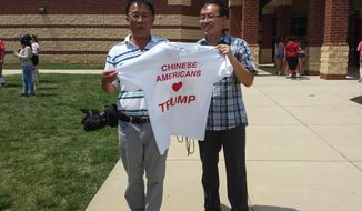 Chinese-Americans Karl Zhang (left) and Samuel Yang hold up a pro-Trump T-shirt at a Donald Trump rally in Ashburn, Virginia, on Aug. 2. (S.A. Miller/The Washington Times)
