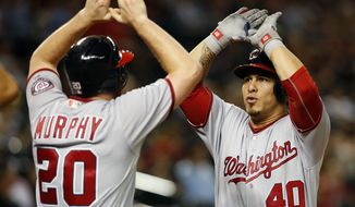Washington Nationals' Wilson Ramos (40) celebrates with Daniel Murphy after Ramos hit a three-run home run against the Arizona Diamondbacks during the fifth inning of a baseball game, Tuesday, Aug. 2, 2016, in Phoenix. (AP Photo/Rick Scuteri) **FILE**
