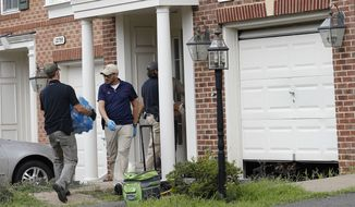 Law enforcement officers work outside the home of Nicholas Young, in Fairfax, Virginia. (Associated Press)