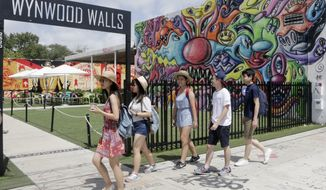 """In this photo taken Monday, Aug. 1, 2016, a group of tourists from Hong Kong tour the Wynwood area of Miami. The CDC has issued a new advisory that says pregnant women should not travel to the so-called Zika """"transmission area"""" in Florida and pregnant women who live there should take steps to prevent mosquito bites and sexual spread of the virus. (AP Photo/Alan Diaz)"""