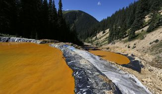 FILE - In this Aug. 14, 2015, file photo, water flows through a series of sediment retention ponds built to reduce heavy metal and chemical contaminants from the Gold King Mine wastewater accident, in the spillway about 1/4 mile downstream from the mine, outside Silverton, Colo. A year after a mine waste spill, residents are taking a break from the aftermath for a party that includes a specially brewed beer the color of the spill. They're also taking a few jabs at the federal Environmental Protection Agency, which accidentally caused the 3-million-gallon spill at the Gold King Mine on Aug. 5, 2015. (AP Photo/Brennan Linsley, File)