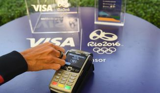 This June 2, 2016 photo shows a Visa payment ring near a payment terminal in New York. Visa, a 30-year Olympics sponsor, is the official payment provider of the Olympics, providing payment infrastructure for the games themselves. This year they are giving 59 of their Olympic athletes a wearable ring that can be used to pay for things by tapping the ring on a payment terminal. (Charles Sykes/AP Images for VISA)