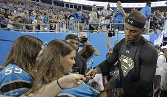 Carolina Panthers' Cam Newton, right, signs autographs at the team's annual Fan Fest practice during NFL training camp in Charlotte, N.C., Friday, Aug. 5, 2016. (AP Photo/Chuck Burton)