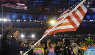 Michael Phelps carries the flag of the United States during the opening ceremony for the 2016 Summer Olympics in Rio de Janeiro, Brazil, Friday, Aug. 5, 2016. (AP Photo/David J. Phillip)