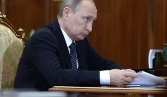 Russian President Vladimir Putin holds papers during a meeting in Moscow's Kremlin on Friday, Aug. 5, 2016. (Alexei Nikolsky/Sputnik, Kremlin Pool Photo via AP)