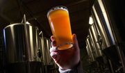 In this Dec. 11, 2013, file photo, brewer Stefano Daneri holding up a beer at Good People Brewing in Birmingham, Ala.  (AP Photo/Dave Martin, File)