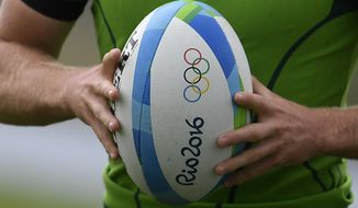 South Africa men's rugby sevens captain Kyle Brown holds a ball with the olympic rings during a training session ahead of the 2016 Summer Olympics in Rio de Janeiro, Brazil, Wednesday, Aug. 3, 2016. (AP Photo/Martin Meissner)