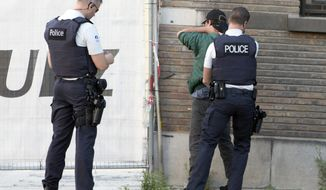 Police officers check identification of a man near the police headquarters in Charleroi, Belgium on Saturday, Aug. 6, 2016, following a machete attack in the area.  A man attacked two police officers with a weapon near the headquarters on Saturday before being apprehended. (AP Photo/Virginia Mayo)