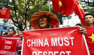 "Filipinos and Vietnamese residents shout slogans while displaying placards during a rally outside the Chinese Consulate to call on China to respect the international arbitration ruling favoring the Philippines on the disputed group of islands in the South China Sea Saturday, Aug. 6, 2016, in the financial district of Makati city east of Manila, Philippines. The protesters denounced China over its continued defiance of the Tribunal ruling and warned it's alleged violations of its obligations ""will surely damage its credibility and worsen its image in the international arena."" (AP Photo/Bullit Marquez)"