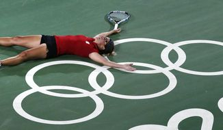 CORRECTS COUNTRY FROM BELARUS TO BELGIUM - Kirsten Flipkens, of Belgium, collapses on the Olympic rings at center court after defeating Venus Williams, of the United States, in three sets at the 2016 Summer Olympics in Rio de Janeiro, Brazil, Saturday, Aug. 6, 2016. (AP Photo/Charles Krupa)
