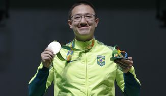 Felipe Wu of Brazil poses for photographers with his silver medal during the award ceremony of the men's 10-meter air pistol event at Olympic Shooting Center at the 2016 Summer Olympics in Rio de Janeiro, Brazil, Saturday, Aug. 6, 2016. (AP Photo/Hassan Ammar)