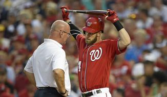 A trainer talks with Washington Nationals' Bryce Harper, right, during his at bat during the third inning of a baseball game against the San Francisco Giants, Saturday, Aug. 6, 2016, in Washington. Harper stayed in the game. (AP Photo/Nick Wass)