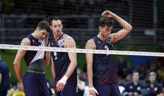 United States' Matthew Anderson, left, David Lee, center, and Aaron Russell stand on the court during a men's preliminary volleyball match against Canada at the 2016 Summer Olympics in Rio de Janeiro, Brazil, Sunday, Aug. 7, 2016. (AP Photo/Jeff Roberson)