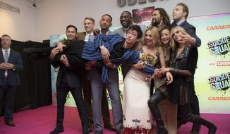 Actors, from centre left to right, Jay Hernandez, Joel Kinnaman, Will Smith, Adewale Akinnuoye, Margot Robbie, Jason Momoa, Karen Fukuhara, Jai Courtney and Cara Delevingne hold Ezra Matthew Miller, upon arrival at the European Premiere of Suicide Squad, at a central London cinema in Leicester Square, Wednesday, Aug 3, 2016. (AP Photo/Joel Ryan)