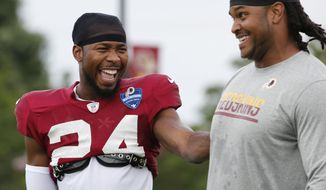 Washington Redskin cornerback Josh Norman, left, jokes with defensive end Ziggy Hood during the afternoon practice at NFL football training camp in Richmond, Va., Tuesday, Aug. 2, 2016. (AP Photo/Steve Helber)