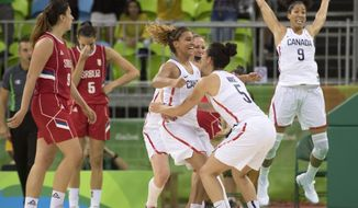 Serbia's Sonja Petroic (5) and Jelena Miovanovic (9) react as Canada's Miah-Marie Langlois, left center, jumps into the arms of teammate Kia Nurse (5) and Miranda Ayim (9) leaps to celebrate winning their preliminary round match at the 2016 Summer Olympics Monday Aug. 8, 2016,  in Rio de Janeiro, Brazil. (Frank Gunn/The Canadian Press via AP)