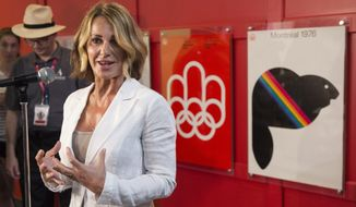 FILE - In this  July 21, 2016, file photo Romania-born gymnastics champion Nadia Comaneci responds to questions as she tours a exhibit marking the 40th anniversary of the Olympic Games in Montreal. Comaneci took to Twitter on August 6, 2016, to correct an internet post that described her as Russian. (Paul Chiasson/The Canadian Press via AP, File)