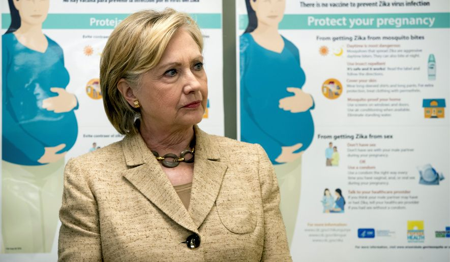 Informational Zika posters for pregnant woman are displayed as Democratic presidential candidate Hillary Clinton takes a tour of a Miami health care center. (Associated Press)