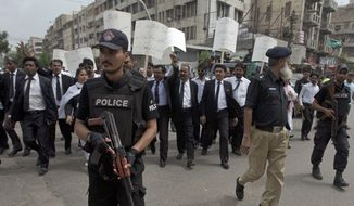 Pakistani police commandos guard lawyers as they hold a demonstration to condemn a Monday suicide bombing, in Karachi, Pakistan, Tuesday, Aug. 9, 2016. Pakistani lawyers are mourning colleagues slain in a shocking suicide bombing the previous day in the southwestern city of Quetta that killed and wounded scores of people, mostly lawyers. (AP Photo/Shakil Adil)