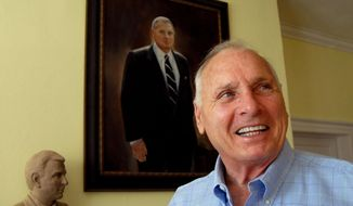 FILE - In this Oct. 4, 2006, file photo, former college football coach Bill Dooley talks about his career as he stands in front of both a portrait and a bust of himself in the living room of his home in Wrightsville Beach, N.C. Former North Carolina, Virginia Tech and Wake Forest coach Bill Dooley has died at the age of 82.  His wife, Marie, said Dooley died Tuesday, Aug. 9, 2016, of natural causes at their home in Wilmington.  Dooley went a combined 162-125-5 in 26 seasons as a head coach with the Tar Heels, Hokies and Demon Deacons and took them to a combined 10 bowl games. AP Photo/Karen Tam, File)