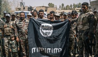 Sheikh Nazhan Sakhar, second from the right, poses for a picture with his men holding an Islamic State flag they captured in Hajj Ali, Iraq, Tuesday, August 9, 2016. Sheikh Nazhan Sakhar and the 700 men under his command are among the forces preparing to retake the Iraqi city of Mosul from the Islamic state group. He says his Sunni militia is critical to defeating IS and maintaining peace afterward because his fighters, unlike the majority of Iraq's military, are local to Mosul. (AP Photo/Alice Martins)