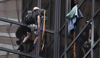 A man attempting to scale Trump Tower talks with a New York Police officer through a window that was broken out by police Wednesday, Aug. 10, 2016, in New York. The man spent more than 2 hours scaling the glass facade of Trump Tower using large suction cups, climbing as high as the 21st floor before police officers grabbed him and hauled him to safety through an open window. (AP Photo/Julie Jacobson)