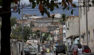 """In this July 22, 2016 photo, residents move about the slum """"Cidade de Deus,"""" or City of God, in Rio de Janeiro, Brazil. The favela was originally a housing project, built in the 1960s during Brazil's military dictatorship when the government evicted residents from favelas in tony Ipanema, Leblon and Lagoa, and destroyed the shacks to make way for visitors. (AP Photo/Silvia Izquierdo)"""