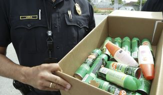 City of Miami police Sgt. Pedro Vera carries a box of insect repellent to hand out to the homeless, Tuesday, Aug. 2, 2016 in the Wynwood neighborhood of Miami. The CDC has advised pregnant women to avoid travel to this neighborhood where mosquitoes are apparently transmitting Zika directly to humans. (AP Photo/Lynne Sladky)