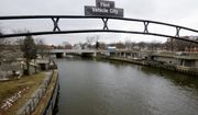 This Jan. 26, 2016, file photo shows a sign over the Flint River in Flint, Mich. (AP Photo/Carlos Osorio)