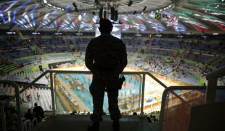 A security official stands guard ahead of a men's preliminary volleyball match between Cuba and Iran at the 2016 Summer Olympics in Rio de Janeiro, Brazil, Thursday, Aug. 11, 2016. (AP Photo/Matt Rourke)