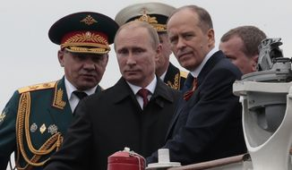 Russian President Vladimir Putin, centre, flanked by Defense Minister Sergei Shoigu, left, and Federal Security Service Chief Alexander Bortnikov, right, arrives on a boat after inspecting battleships during a navy parade marking the Victory Day in Sevastopol, Crimea, Friday, May 9, 2014. (Associated Press) ** FILE **