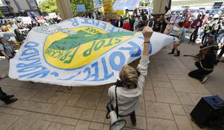 Protesters wave a banner during an attempt to disrupt a federal auction of drilling rights at a hotel in Lakewood, Colorado, on May 12. More than 200 people turned out to protest the Bureau of Land Management sale. (Associated Press)