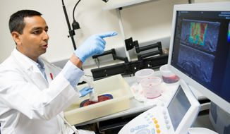 Research and Development Engineer Avinash Eranki examines a donated placenta as researchers are working to create a 3D bioprinted version to study preeclampsia at Children's National Medical Center, in Washington, Wednesday, June 15, 2016. Researchers are looking into how problems with the placenta lead to health threats from preeclampsia to Zika. (AP Photo/Andrew Harnik)