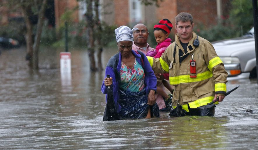 A member of the St. George Fire Department assists residents as they wade through floodwaters from heavy rains in the Chateau Wein Apartments in Baton Rouge, La., Friday, Aug. 12, 2016. (AP Photo/Gerald Herbert)