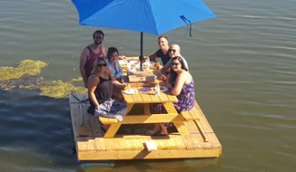 In an Aug. 7, 2016 photo, Caleb Keller, rear right, and his wife, Meagan, front left, enjoy a ride on their picnic table boat with a group of friends on Speedwell Forge Lake, in Lancaster, Pa. (Keith Schweigert/LNP Media Group, Inc. via AP)