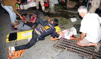 In this Thursday, Aug. 11, 2016, photo, the injured are helped after a bomb blast in the southern resort city of Hua Hin, 240 kilometers (150 miles) south of Bangkok, Thailand. Police are investigating a series of bomb blasts in Hua Hin and other cities in Thailand. (Daily News via AP)