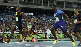 Jamaica's Usain Bolt, left, crosses the line to win gold in the men's 100-meter final during the athletics competitions of the 2016 Summer Olympics at the Olympic stadium in Rio de Janeiro, Brazil, Sunday, Aug. 14, 2016. (AP Photo/Matt Slocum)