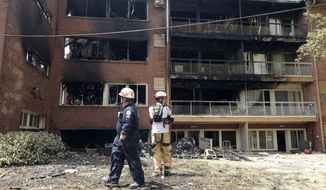In this Thursday, Aug. 11, 2016, file photo, emergency personnel view the scene of an apartment building fire in Silver Spring, Md. (AP Photo/Susan Walsh, File)