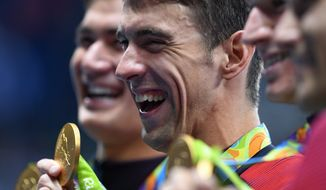 United States' Michael Phelps celebrates with teammates during the medal ceremony for the men's 4 x 100-meter medley relay final during the swimming competitions at the 2016 Summer Olympics, Sunday, Aug. 14, 2016, in Rio de Janeiro, Brazil. (Sean Kilpatrick/The Canadian Press via AP)