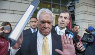 In this March 10, 2014, file photo, Jeffrey Thompson holds up his hands to indicate he will not speak to reporters as leaves federal court in Washington, after being charged in a criminal information with two conspiracy offenses stemming from an ongoing investigation. Thompson, a District of Columbia businessman who poured millions of illegal dollars into city, state and federal elections has been sentenced to three months in prison. (AP Photo/Cliff Owen, File)