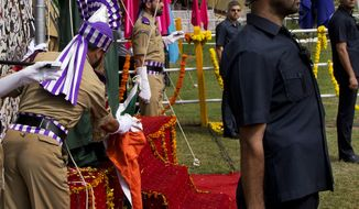 Jammu and Kashmir state Chief Minister Mehbooba Mufti, in green dress, watches as she holds the rope attached to India's national flag after it fell during the unfurling ceremony on India's Independence Day in Srinagar, Indian controlled Kashmir, Monday, Aug. 15, 2016.  Authorities ordered a probe to ascertain if it was a sabotage or negligence after India's national flag fell on the top elected official as she pulled the rope to unfurl the flag at the highly guarded soccer stadium. (AP Photo/Dar Yasin)