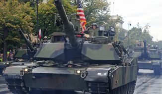 A group of American tanks and soldiers take part in a yearly military parade marking the Polish Army Day, in Warsaw, Poland, Monday, Aug. 15, 2016, in a symbolic show of increased U.S. military involvement in a region shaken by a more assertive Russia. (AP Photo/Alik Keplicz)