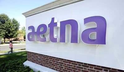 A pedestrian walks past a sign for Aetna Inc., at the company headquarters in Hartford, Conn. (Associated Press)