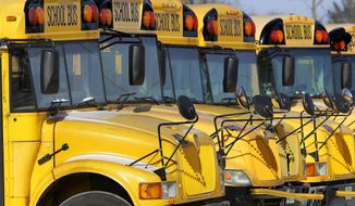 In this Jan. 7, 2015, file photo, public school buses are parked in Springfield, Ill. (AP Photo/Seth Perlman, File)