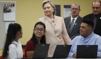 Democratic presidential candidate Hillary Clinton talks with students as she tours classrooms at John Marshall High School in Cleveland, Wednesday, Aug. 17, 2016, before participating in a campaign event. Stands behind Clinton at right is Eric Gordon Chief Executive Officer, Cleveland Metropolitan School District, and David Quolke, President, Cleveland Teachers Union, second from right. (AP Photo/Carolyn Kaster)