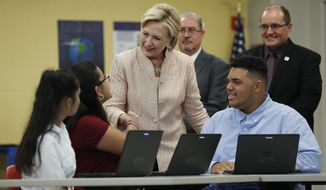 Democratic presidential candidate Hillary Clinton talks with students as she tours classrooms at John Marshall High School in Cleveland, Wednesday, Aug. 17, 2016, before participating in a campaign event. Standing behind Clinton at right is Eric Gordon, Chief Executive Officer, Cleveland Metropolitan School District, and David Quolke, President, Cleveland Teachers Union, second from right. (AP Photo/Carolyn Kaster)