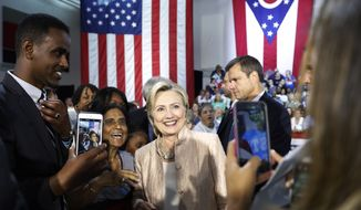 Democratic presidential candidate Hillary Clinton poses for a cell phone photos with people in the audience after speaking at campaign event at John Marshall High School in Cleveland, Wednesday, Aug. 17, 2016. (AP Photo/Carolyn Kaster)