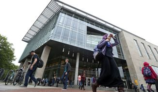 Students walk by the renovated James Branch Cabell Library on the campus of Virginia Commonwealth University in Richmond, Va., on April 28, 2016. Hundreds of schools have reinvented their libraries in recent years as colorful hubs of college life. Gone are bound journals, miles of steel shelving, and old rules governing proper behavior. In are on-site cafes, group study areas where talking is encouraged, 24-hour access and sofas designed for dozing. (AP Photo/Steve Helber)