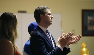 Eric Trump, son of Republican presidential candidate Donald Trump, applauds as Trump speaks to retired and active law enforcement personnel at a Fraternal Order of Police lodge during a campaign stop in Statesville, N.C., Thursday, Aug. 18, 2016. At left is Eric's wife Lara Yunaska. (AP Photo/Gerald Herbert)