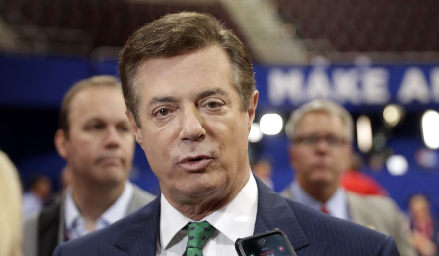 Trump campaign chairman Paul Manafort talks to reporters on the floor of the Republican National Convention at Quicken Loans Arena in Cleveland on July 17, 2016, as Rick Gates listens at back left. (Associated Press) **FILE**